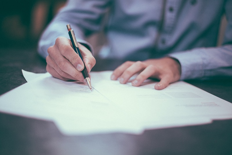 man's hands signing document with pen