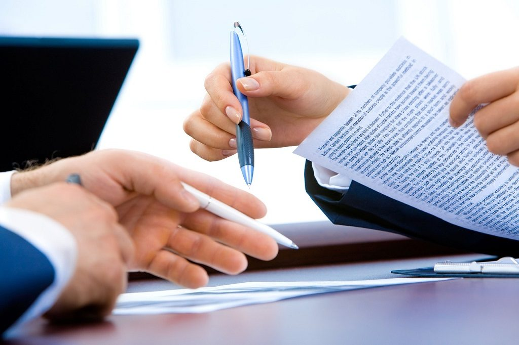 man and woman holding pens pointing at document